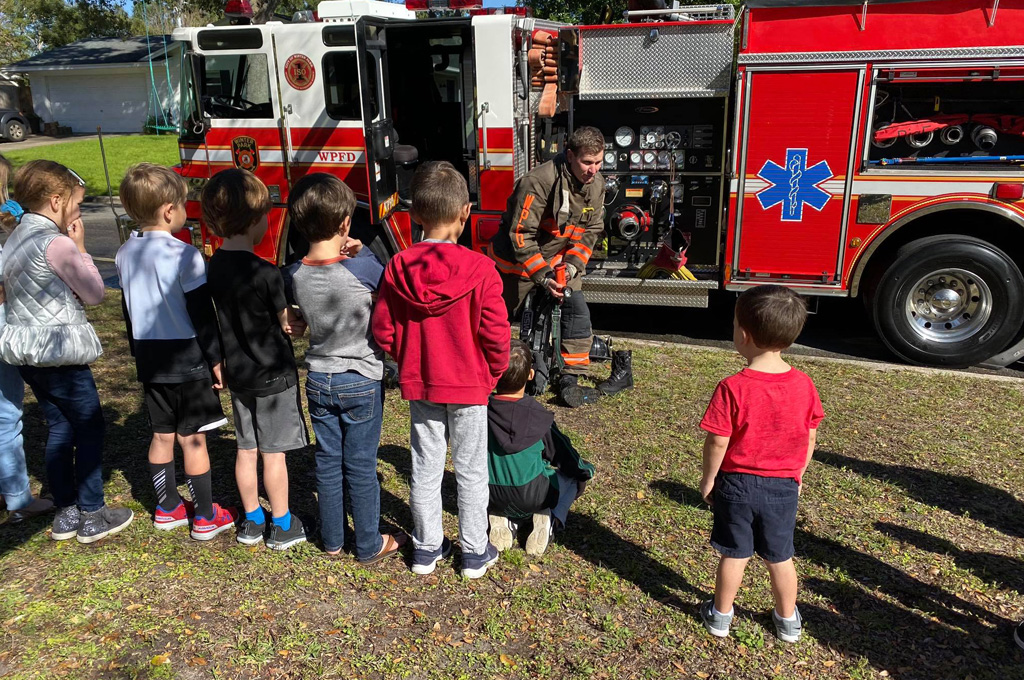 Firefighter addressing a group of young children beside a fire truck about fire safety.