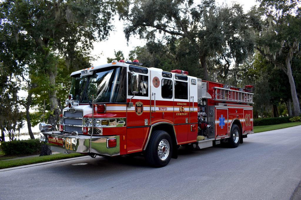 Engine 61 parked on a street in front of a lake with trees.