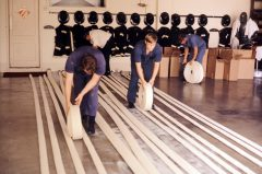 Old photo of firefighters rolling up hoses at the station.