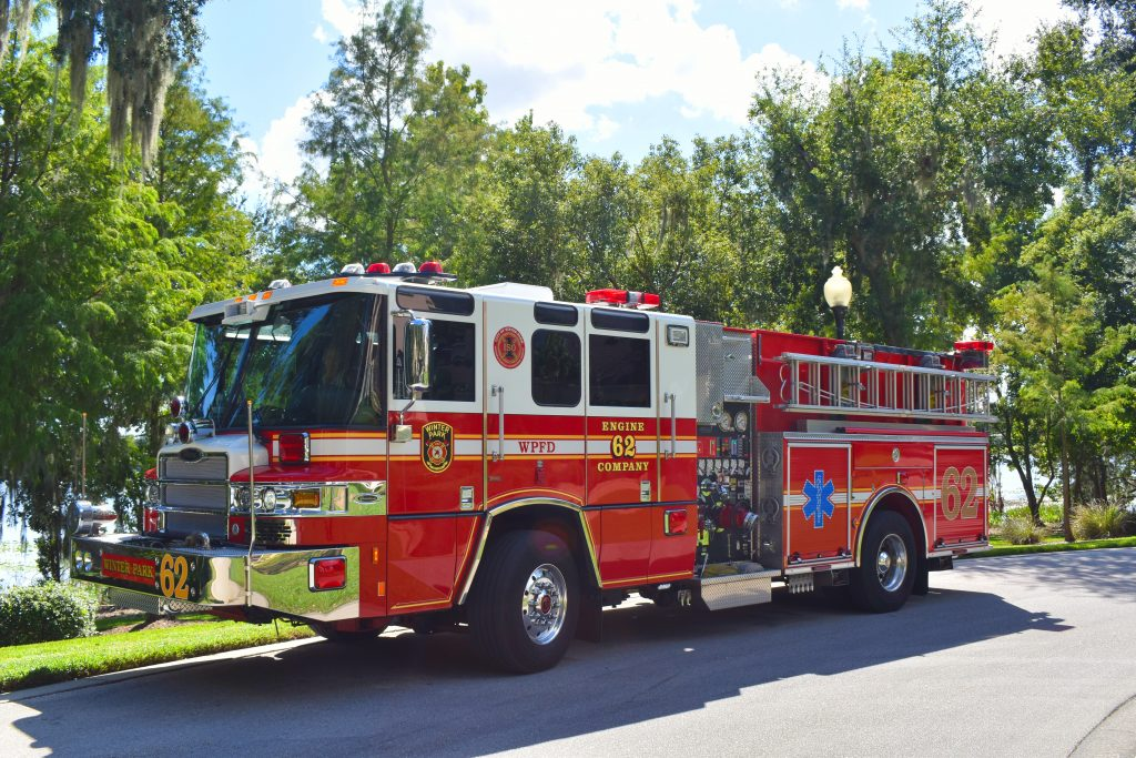 2016 Pierce Quantum ALS Pumper parked on street in front of trees and a lake.