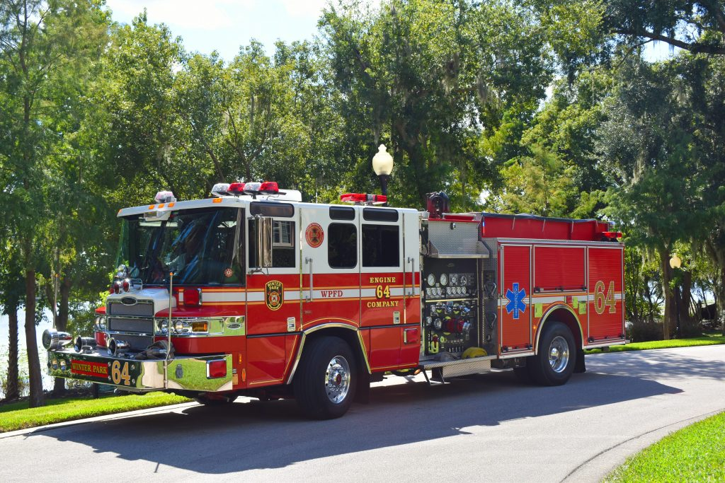 2001 Pierce Quantum ALS Pumper parked on street in front of trees and a lake.
