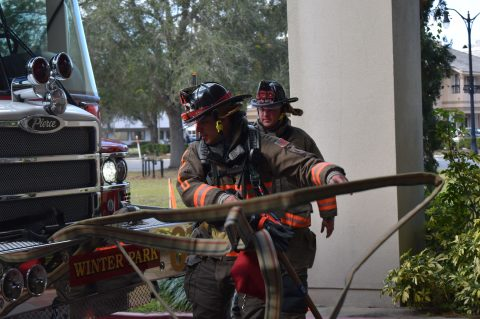 Two firefighters unloading hose from the front of the engine.