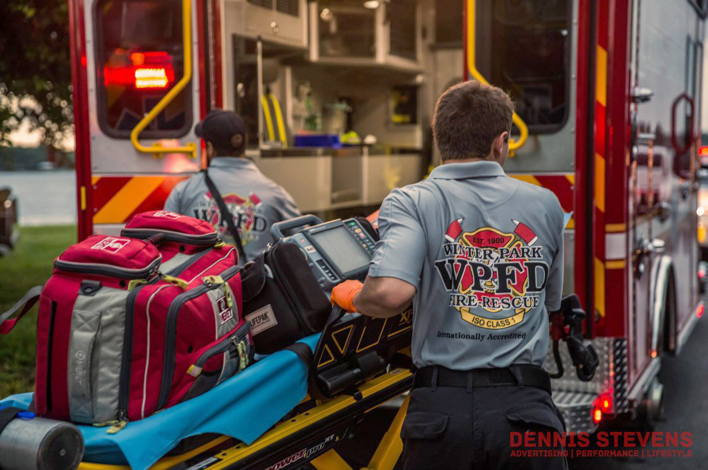 Firefighter / Paramedic pulling a stretcher and first-aid kit towards the opened back of an ambulance.