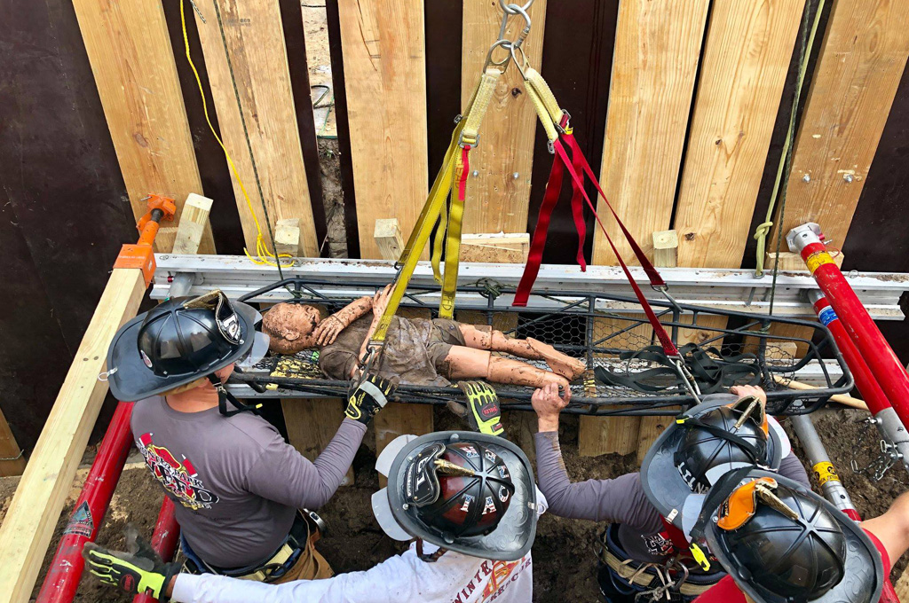 Firefighters lifting a training manikin up on a stretcher while performing trench rescue exercises.