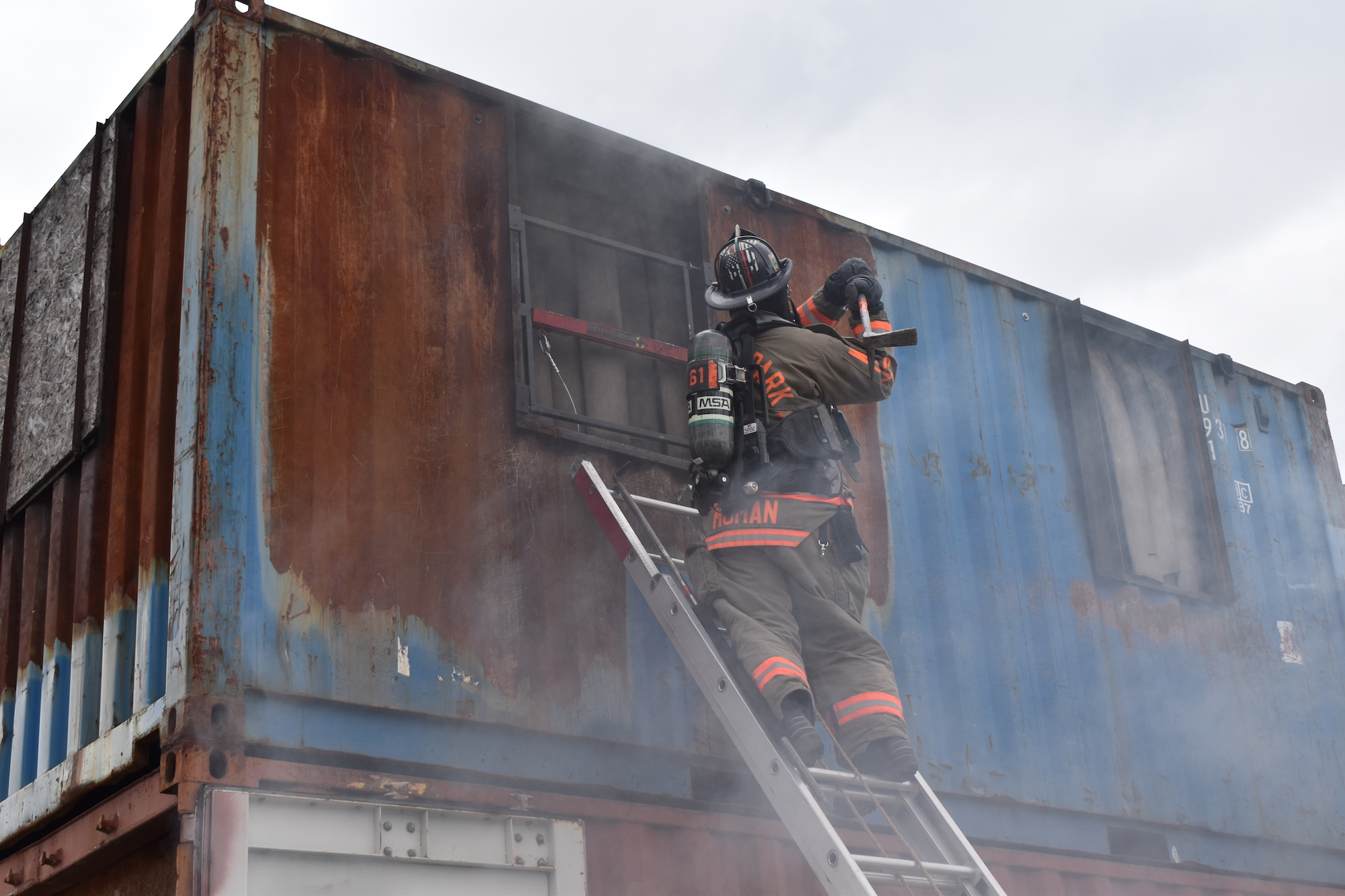 Firefighter climbing a ladder to a second story container building during live burn training.