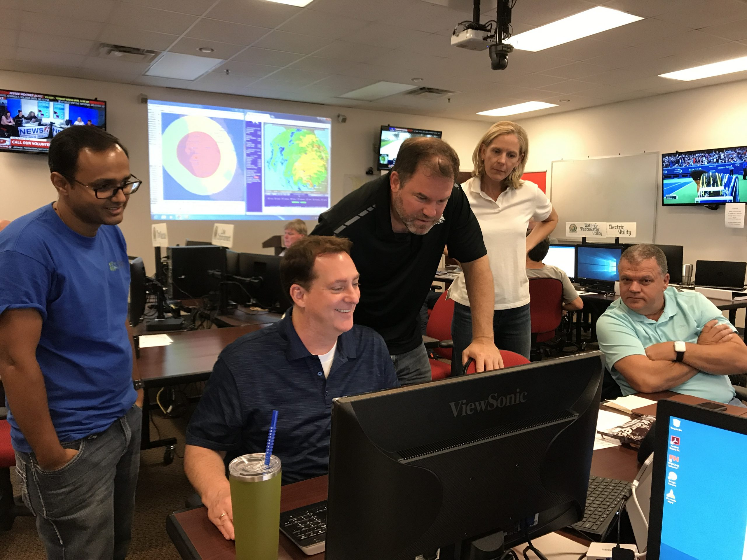 Group of people huddled around a computer with a hurricane on the television in the background.