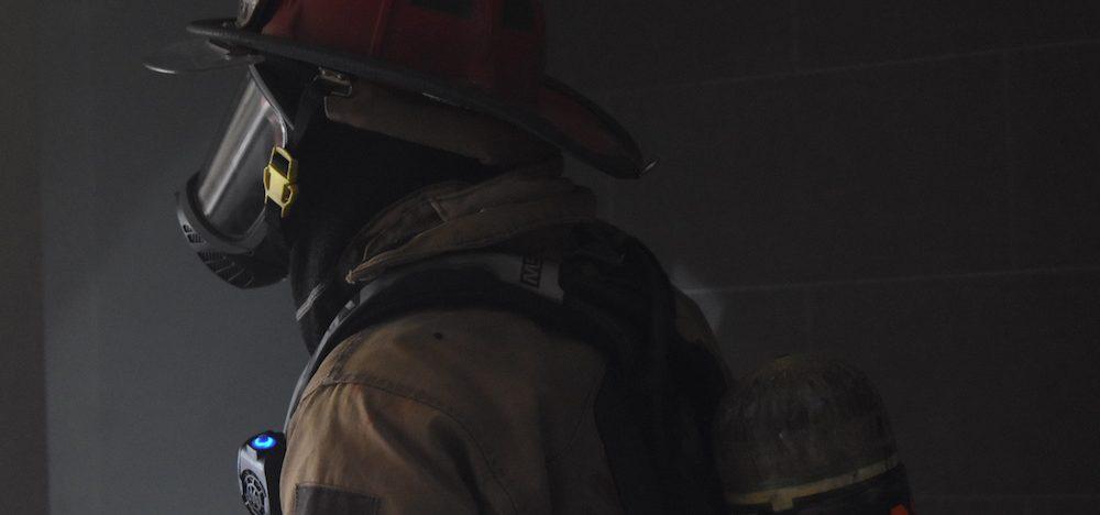 Firefighter walking through smokey building