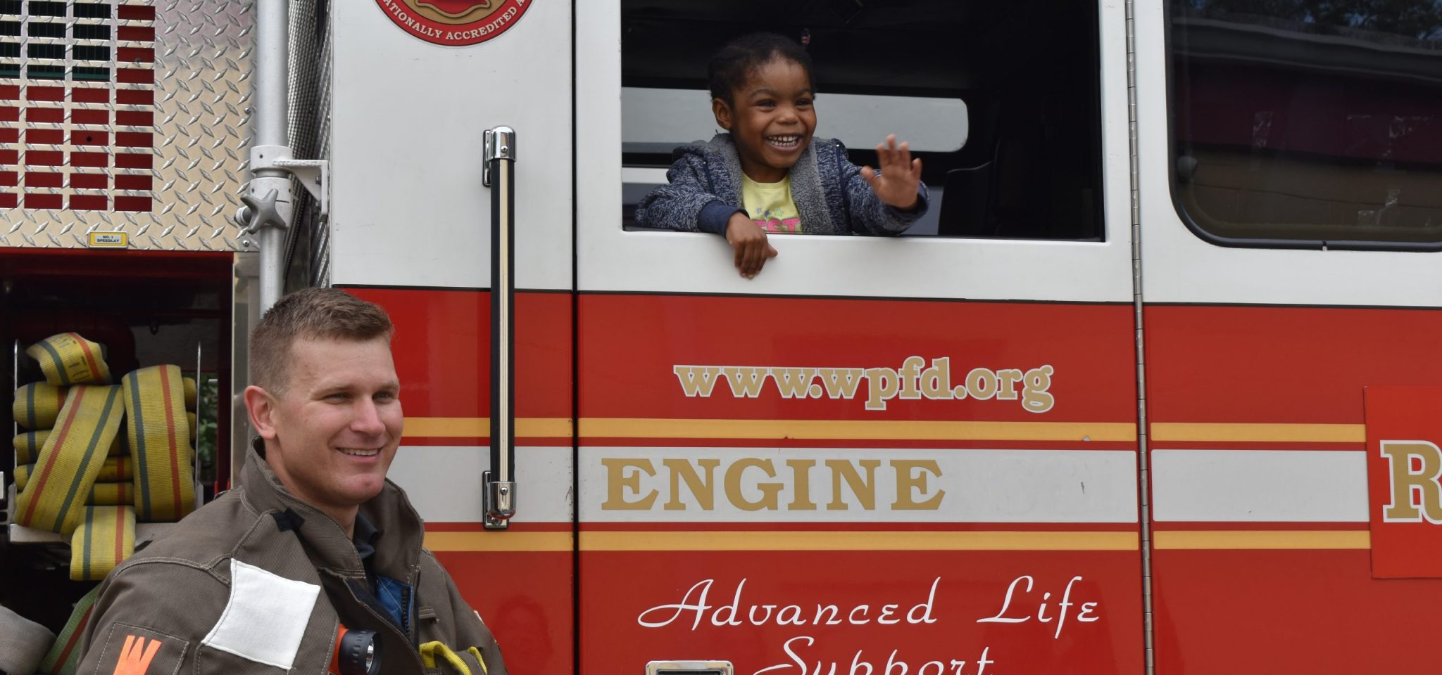 Firefighter posing for photo with young girl