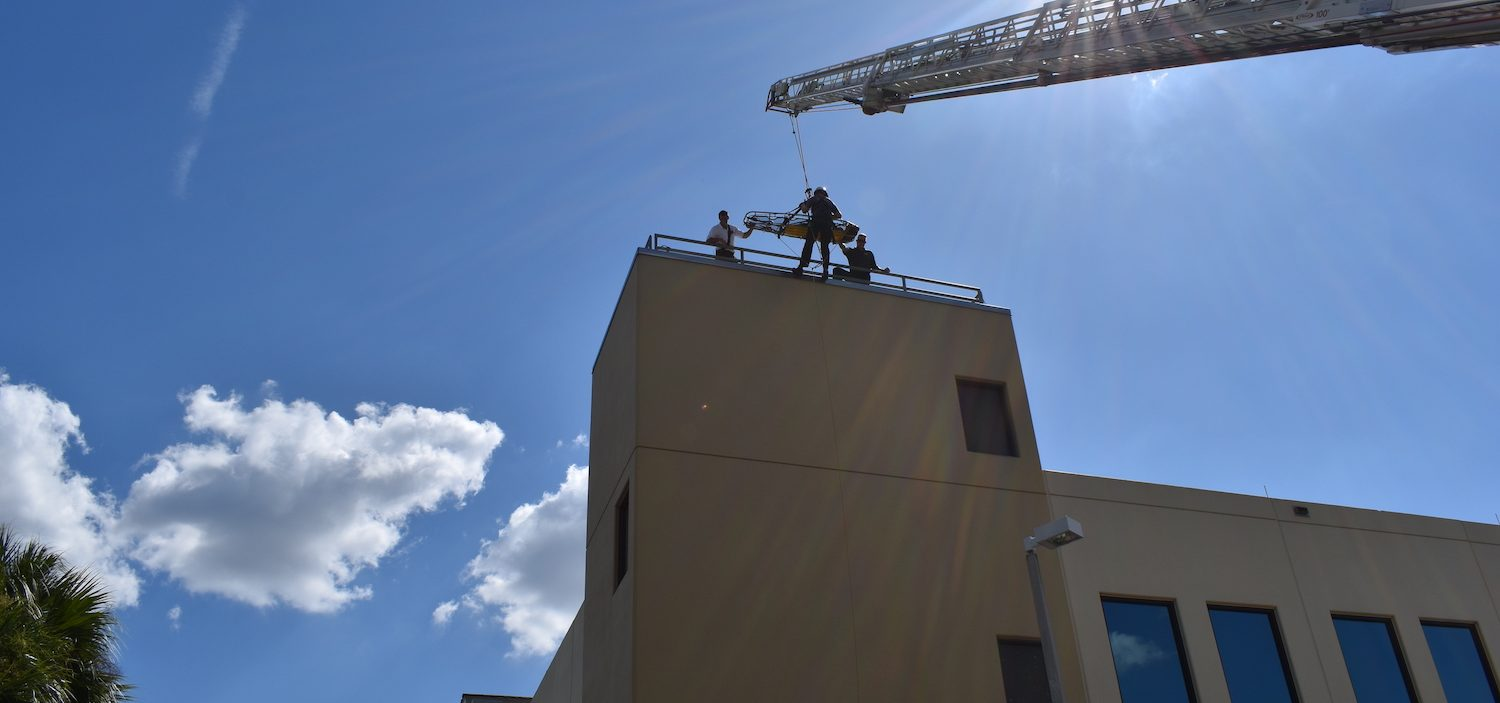 Firefighters on the top of a building utilizing the ladder truck