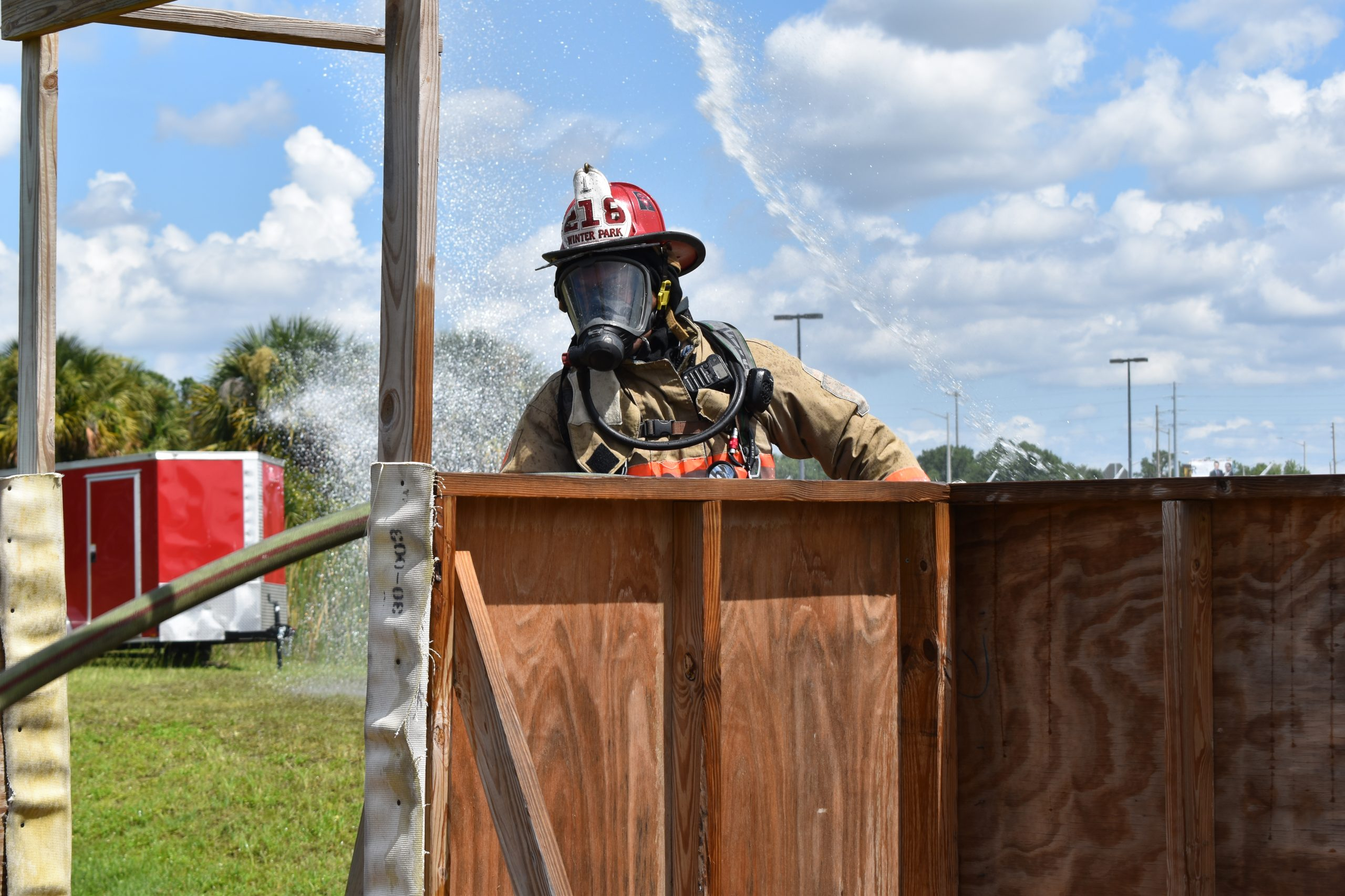 Firefighter pulling a hose line inside a small structure.
