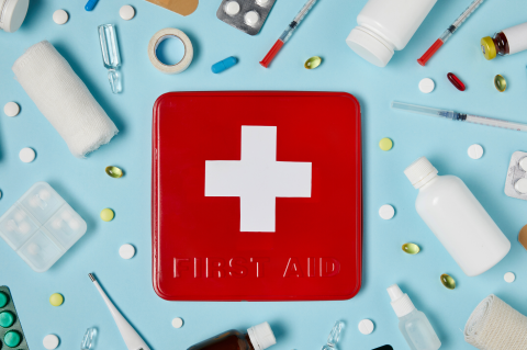 First aid kit surrounded by medicine, bandages, and liquid on a light blue background.