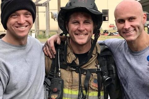 Three men standing together, one in full firefighter gear