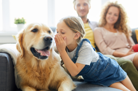 Family with girl whispering into a golden retreiver's ear.