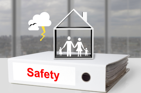 Black and white graphic with stick figures inside a stick home on top of a binder that says safety